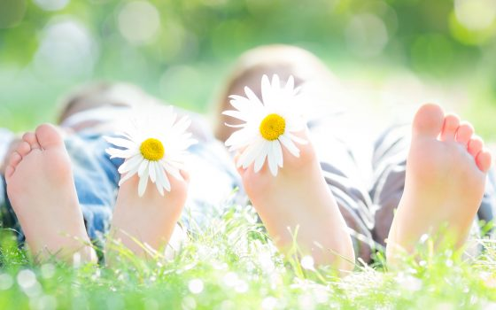 Kids laying on grass in summer