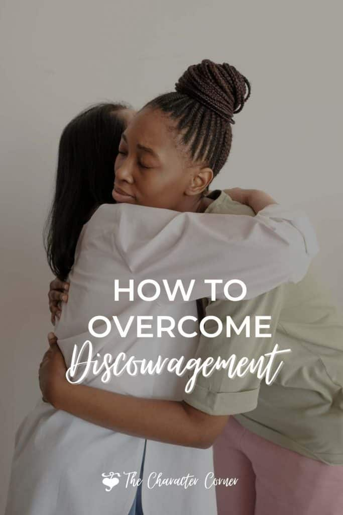 Image reads how to overcome discouragement. Shows two women hugging each other in support.