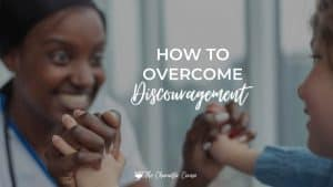 Image reads How to overcome discouragement. Shows two women grasping hands in encouragement.